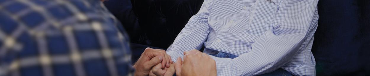 Homme qui soutient son père en lui tenant les mains suite à une récidive de cancer