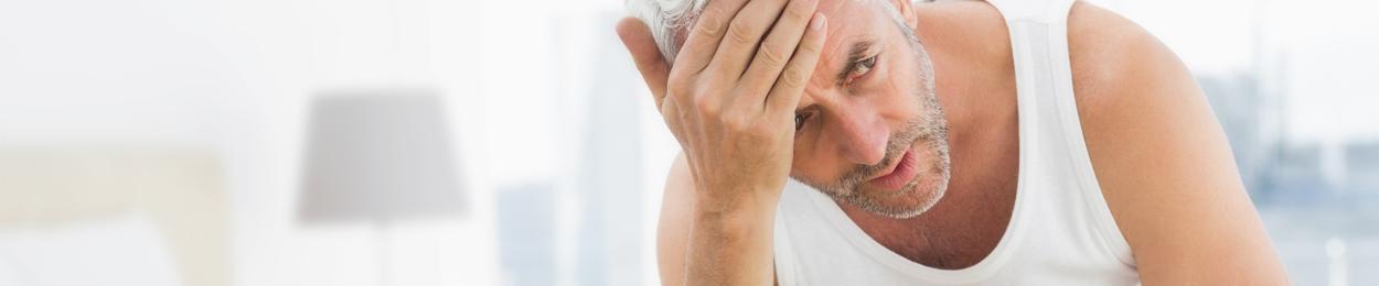 Homme assis sur son lit suite à un effets secondaires de son traitement