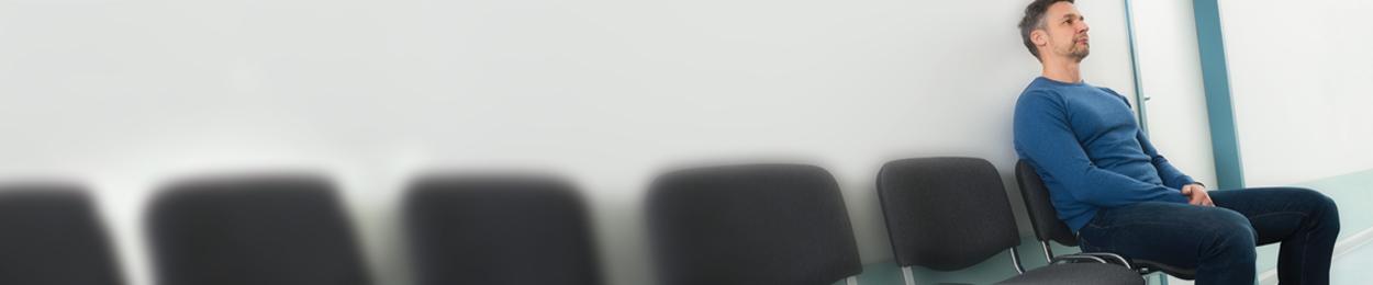 Homme à risque du cancer de la prostate assis seul dans une salle attendant son tour