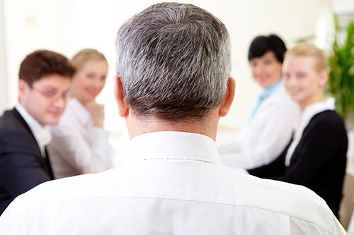 Homme vu de dos devant ses collègues et employés lors d