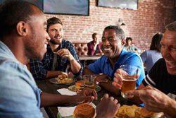 Jeunes hommes à risques d'un cancer de la prostate dans un bistro mangeant de la malbouffe