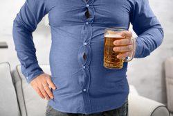 Zoom sur un gros ventre avec une bière à la main illustrant les facteurs de risque du cancer de la prostate