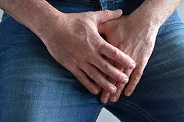 Mains placées à la hauteur du pubis et de la prostate
