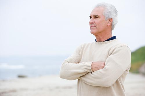 Homme debout les bras croisés suite à un diagnostic de cancer de la prostate