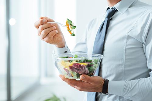 Homme d'affaire debout et mangeant une salade