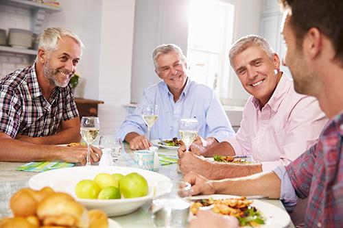 Hommes à risque de prostatite discutant autour en mangeant