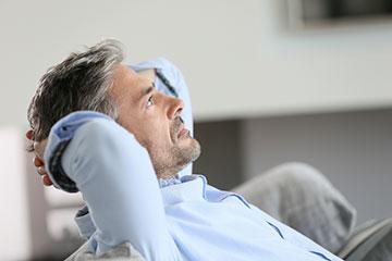 Bien connaitre ses options pour prendre une décision éclairée - Homme assis mains derrière le cou pensant aux choix de traitements de son cancer de la prostate