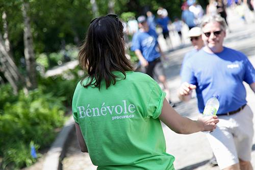 Bénévole vue de dos tendant une bouteille de H2O à un participant de la Marche du Courage PROCURE