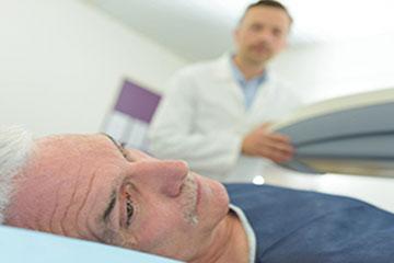 Homme étendu prêt pour la radiothérapie de son cancer de la prostate