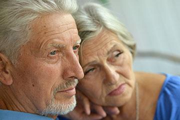 Un couple enlacé qui écoute le médecin annoncer une récidive de cancer