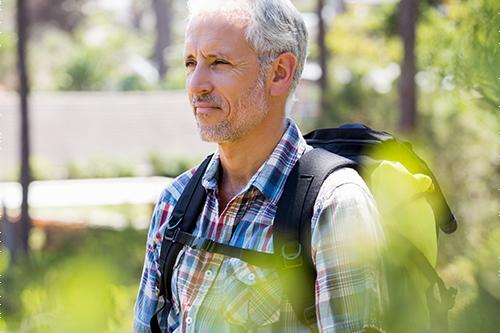Homme qui fait une randonnée avec sac à dos malgré un cancer avancé